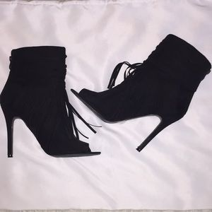 Black fringe peep toe boots with a heel.